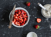 Chopped strawberries and the jar with whole grain flour on a dark background. Ingredients for making strawberry pie Stock Photography