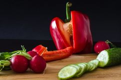 Chopped sweet pepper paprika and other vegetables. Chopped sweet pepper paprika, green sliced cucumber, radishes with Royalty Free Stock Images
