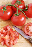 Chopped tomatoes. Fresh, ripe tomatoes on the vine with chopped tomatoes to the side Royalty Free Stock Photography