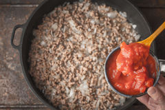 Chopped tomatoes in the ceramic bowl with blurred pot top view Stock Photos