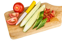 Chopped tomatoes and cucumbers on wooden cutting board Stock Images