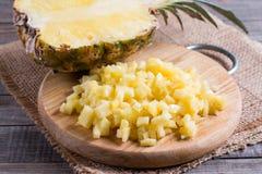Chopped torkade ananasstycken på träskärbräda arkivfoto