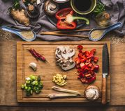 Chopped vegetables for stir fry cooking on wooden cutting board on kitchen table background with ingredients, top view. Asian food Royalty Free Stock Images