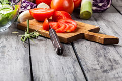 Chopped vegetables: tomatoes on cutting board Royalty Free Stock Images
