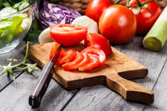 Chopped vegetables: tomatoes on cutting board Royalty Free Stock Photos