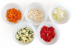 Chopped vegetables in white bowls, cooking preparation. Different kinds of chopped vegetables in white bowls, cooking preparation Royalty Free Stock Photos