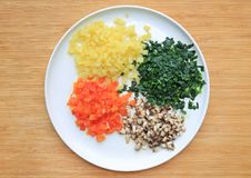 Chopped vegetables on white plate against wooden board background royalty free stock photo