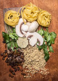 Chopped walnuts, raisins, mushrooms, herbs concept cooking   a cutting board on wooden background top view Stock Photo