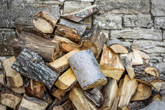 Chopped wood besides stone wall Stock Photography