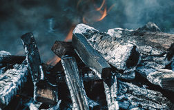 Chopped wood burns and smokes in the grill. Royalty Free Stock Images