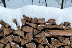 Chopped wood covered in snow. Chopped wood stacked on a heap and covered in snow Stock Images