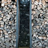 Chopped wood stacked in two heaps. Cut wood standing in two stacks Royalty Free Stock Photos