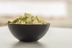 Chopped zucchini in a bowl  on white Royalty Free Stock Images