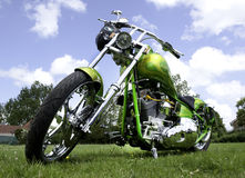 Chopper. Seen from below a custom paited chopper motorcycle on grass and with chrome finished engine stock photo