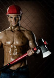 Chopper. The beauty muscular worker chopper man, in safety helmet with big heavy ax in hands, on netting fence background royalty free stock photography