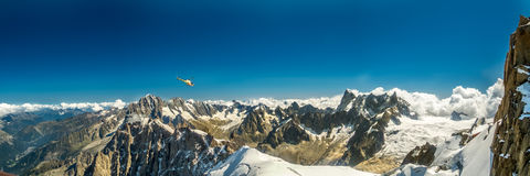 Chopper flies over peaks Royalty Free Stock Photography