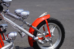 Chopper front wheel. The front wheel of a chopper motorcycle with red mudguard and shiny chrome front forks Royalty Free Stock Photo