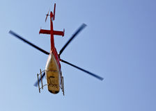 Chopper helicopter heading north south east west. Horizontal take of an orange and white chopper flying overhead at Katra Heliport Northern India used to ferry stock image