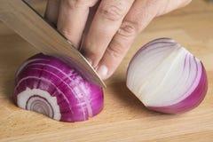 Choppig del cocinero una cebolla roja con un cuchillo Fotografía de archivo