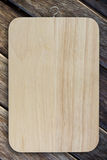 Chopping board. Wooden chopping board on wood background Royalty Free Stock Photos
