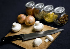 Chopping board. With various herbs and spices. Onions, knife and mushrooms on the board royalty free stock photo