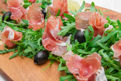 Chopping board with aragula and raw ham Stock Photo