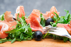 Chopping board with aragula and raw ham Royalty Free Stock Photos