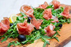 Chopping board with aragula and raw ham Royalty Free Stock Image