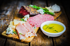 Chopping board of Assorted Cured Meats, Cheese and Honey with ro Royalty Free Stock Photos