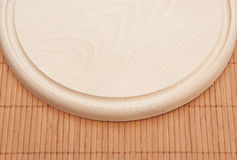 Chopping board on bamboo placemat Royalty Free Stock Photos