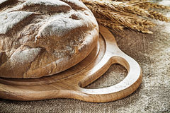 Chopping board bread wheat ears on vintage hessian background.  stock photos