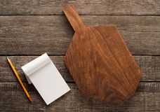 Chopping board and cookbook on wooden background Stock Photo