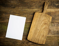 Chopping board and empty page on rustic background.  Stock Image