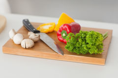 Chopping board in a kitchen with red and yellow pepper Stock Photos