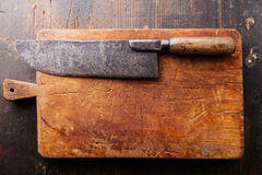 Chopping board and Meat cleaver. On dark wooden background stock image