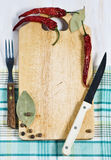 Chopping board, pepper, fork and knife Stock Photo