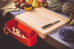 Chopping Board with Red Waste Container with Fresh Fruits Background. Healthy Eating Vegan Raw Food Concept stock photos
