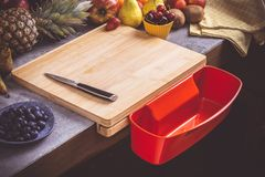 Chopping Board with Red Waste Container with Fresh Fruits Background. Healthy Eating Vegan Raw Food Concept royalty free stock photos