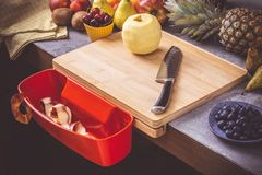 Chopping Board with Red Waste Container with Fresh Fruits Background. Healthy Eating Vegan Raw Food Concept royalty free stock photography