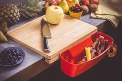 Chopping Board with Red Waste Container with Fresh Fruits Background. Healthy Eating Vegan Raw Food Concept stock image