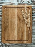 Chopping board rye ears on vintage wooden surface Royalty Free Stock Photos