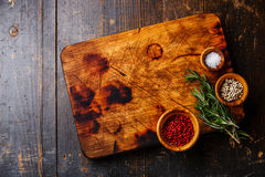 Chopping board, salt, pepper and rosemary Stock Photography
