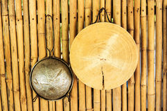 Chopping board and strainer. Hanging on a bamboo wall in an outdoor kitchen stock photo
