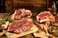 Chopping board with various meats. Old wooden table and chopping board covered with raw uncooked t-bone, rib tips and flank parts, cote de boeuf, beside royalty free stock photography