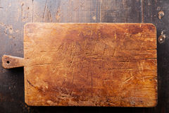 Chopping board on wooden background Royalty Free Stock Photos