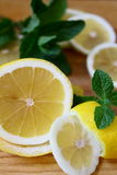 On the chopping board. Yellow lemon with fresh sprig of mint. Yellow lemon with fresh sprig of mint Royalty Free Stock Images