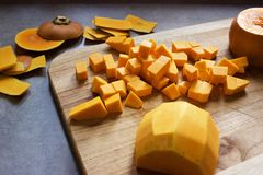 Chopping butternut squash into cubes on a wooden cutting board Stock Photo