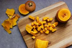 Chopping butternut squash into cubes on a wooden cutting board Stock Image