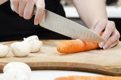 Chopping carrots on a chopping board Royalty Free Stock Images