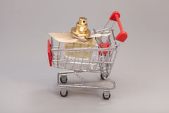 Chopping cart with woman perfume bottle royalty free stock photography